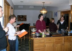 People gathered around a kitchen during one of Madhu's cooking classes.